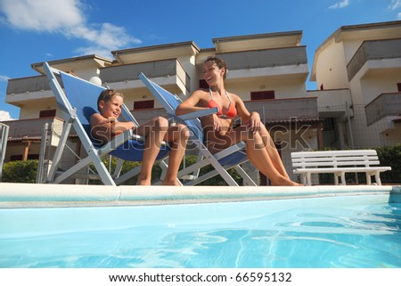 young mother in orange pareo and son sitting on beach chair near pool and smiling, house