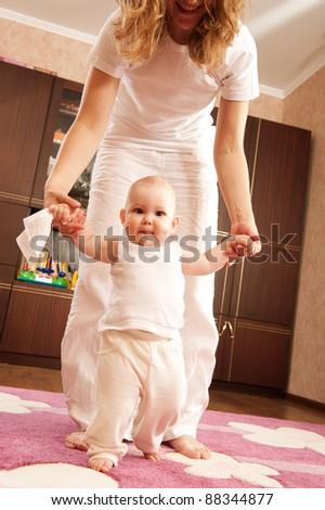 Young mother is helping her daughter to make first steps