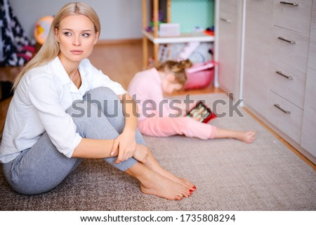 Young mother is nervous and sad at home on the floor, the child watches cartoons on the tablet and plays, naughty child, family concept.