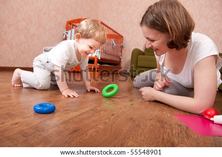 Young mother is playing with her little son