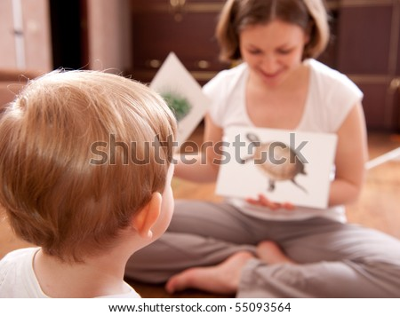 Young mother is showing cards with animals to her little son