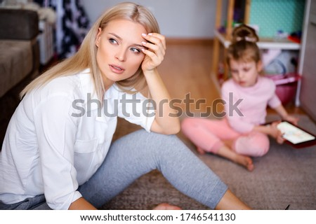 Young mother is worried and sad at home on the floor, the child is watching cartoons on the tablet and playing, a naughty child, family concept.