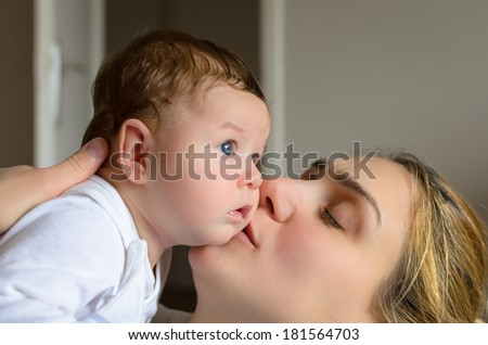 Young mother kissing her adorable baby boy in a room