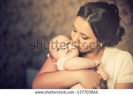 Young mother kissing her little newborn baby Stock photo ©