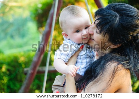 Young mother kissing her little son in park