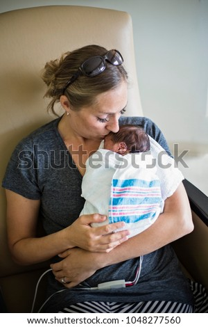 Young mother kissing her Premature newborn baby who is being treated in the hospital. With love and tenderness she holds her baby close Foto stock ©