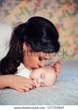 Young mother kissing her small sleeping newborn baby
