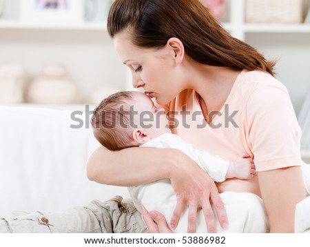 Young mother kissing her small sleeping newborn baby - indoors