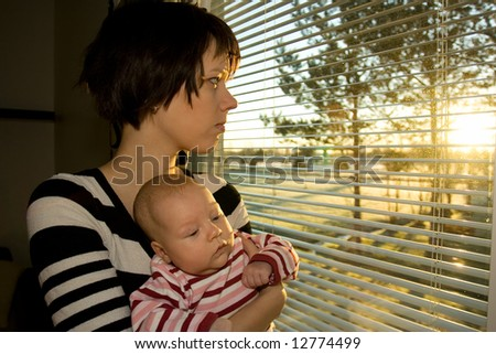 Young mother looking out from the window with her baby