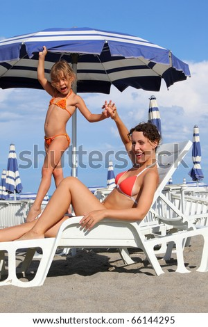 young mother lying on lounger under beach umbrella. little daughter standing near mother and holds her hand. in background rows of white loungers and blue umbrellas