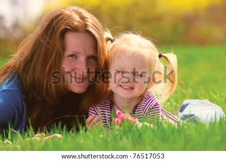 young mother lying with child girl on a grass at the park