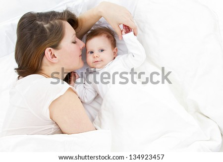 young mother lying with her baby in a white bed