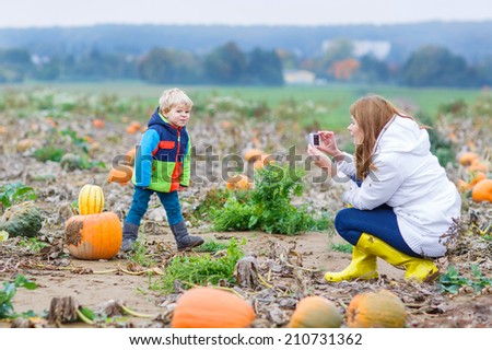 Young mother making picture on mobile phone of her child on pumpkin patch