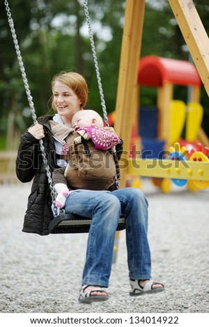 Young mother on a swing with baby in a babycarrier