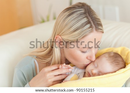 Young mother on the sofa kissing her baby
