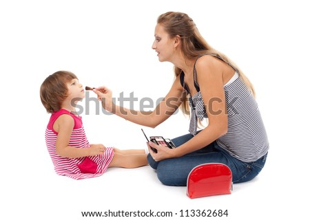 Young mother paints little girl cosmetics on white background