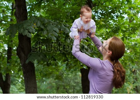 Young mother playing with a laughing baby girl in a park