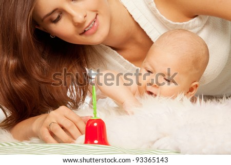 Young mother playing with baby in the bed with toy bell