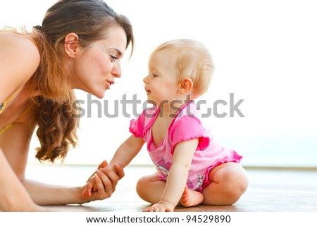 Young mother playing with baby on floor
