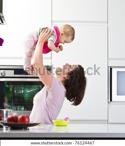 Young mother playing with her baby daughter in a modern kitchen setting. - stock photo