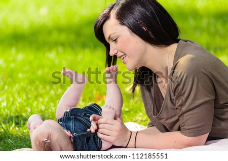 Young mother playing with her baby daughter on grass.