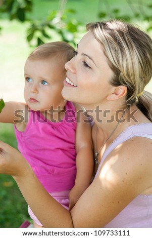 Young mother playing with her baby girl outdoors in the garden