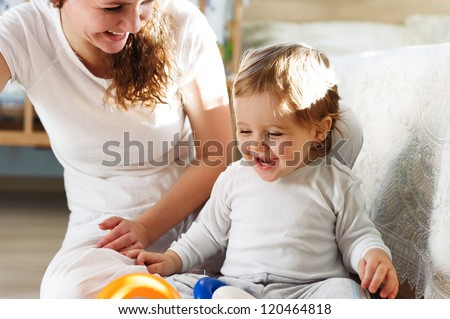 Young mother playing with her baby son at home - stock photo
