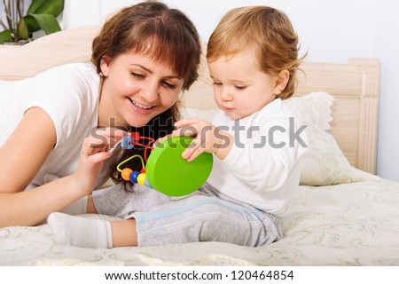 Young mother playing with her baby son at home