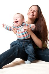 young mother playing with her cute smiling baby, isolated on white background