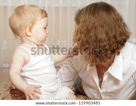Young mother playing with her little daughter at home