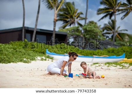 Young mother playing with her little son on a tropical beach
