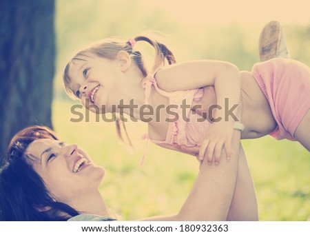 Young mother playing with little daughter in green summer park
