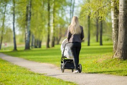 Young mother pushing white baby stroller and slowly walking at town green park in warm, sunny spring day. Spending time with infant and breathing fresh air. Enjoying stroll. Back view.