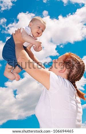 Young mother raising up her baby boy into the air - stock photo