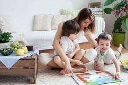 Young mother, read a book to her two children, boys, in the living room, eating fruits and drinking smoothie, mothers day concept