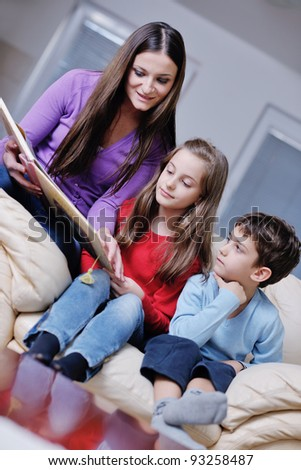 young mother read book to their kids at modern new home living room indoor