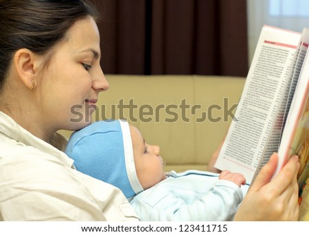 Young mother reading a book together with her baby