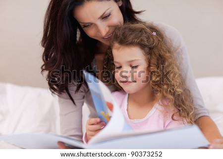Young mother reading a book with her daughter - stock photo