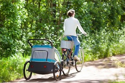 Young mother riding bicycle with baby bike trailer in sunny summer park. Fit active woman cycling with child. Safe transportation of little kids. Mom and children riding bikes. Family outdoor activity