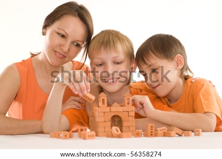 young mother sitting at the table with two sons