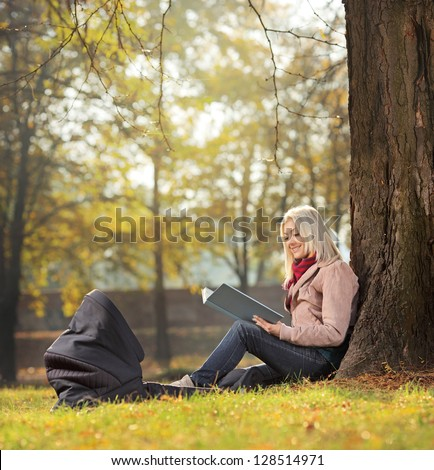 Young mother sitting in a park with her baby in a carrycot and reading a story, shot with a tilt and shift lens - stock photo