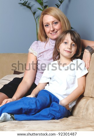 Young mother sitting on the sofa with her 6 year old son