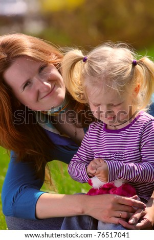 young mother sitting with child girl on a grass at the park