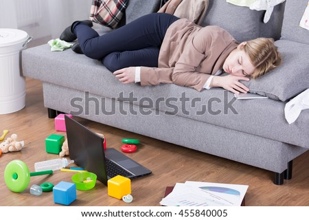 Young mother sleeping in her office clothes on a sofa in a messy living room #455840005