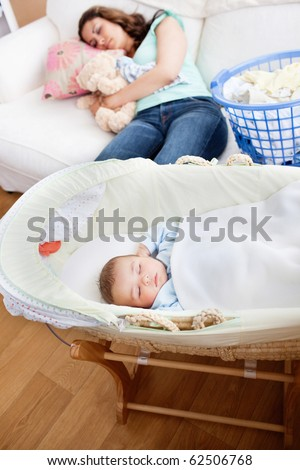 Young mother sleeping on the sofa while her baby is sleeping in his cradle in the living-room at home