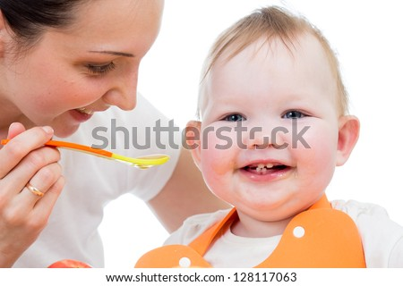 young mother spoon-feeding happy daughter