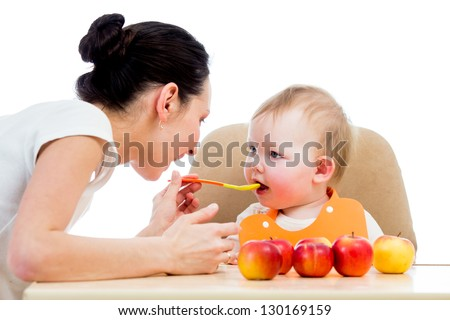young mother spoon-feeding her baby girl