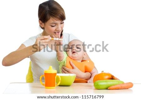 young mother spoon feeding her baby isolated on white