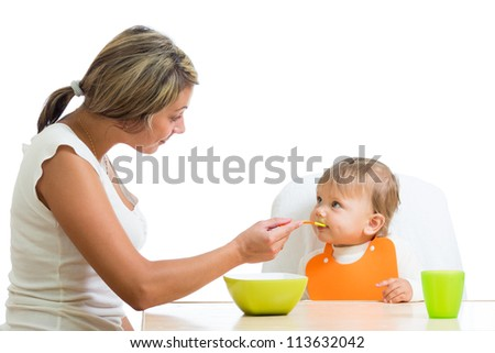 young mother spoon feeding her cute baby girl isolated on white