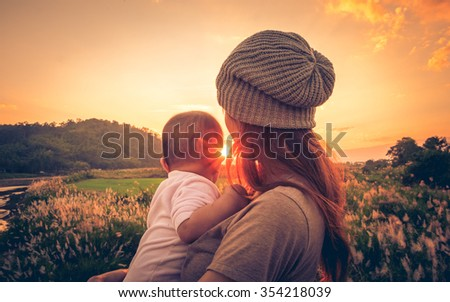 Young mother standing near a river & carrying her baby looking at the beautiful Sunset. Also Seeing a beautiful green field & mountain on a background.  ストックフォト ©